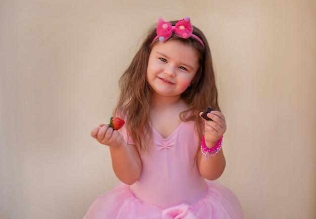 Portrait d'un enfant en robe de ballet. fille posant, tenant un morceau de chocolat et une fraise dans ses mains, souriant