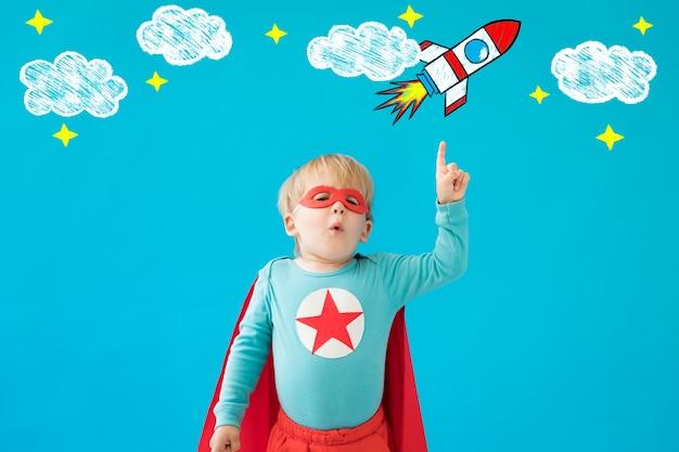 Portrait d'enfant de super-héros. enfant de super héros contre le mur bleu.