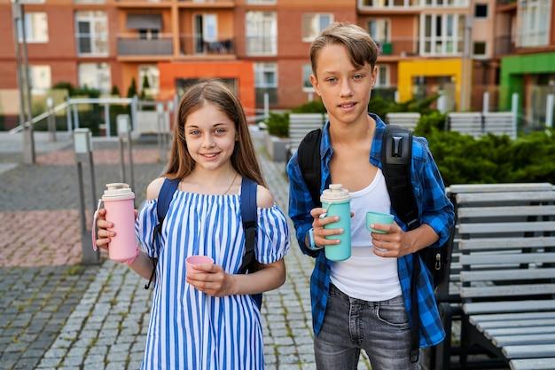 Portrait d'enfants amis garçon et fille près de l'école buvant du thé dans un thermos bleu et rose.