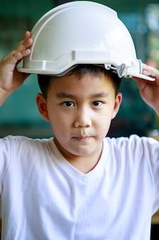 Portrait d'enfants asiatiques et casque de sécurité blanc