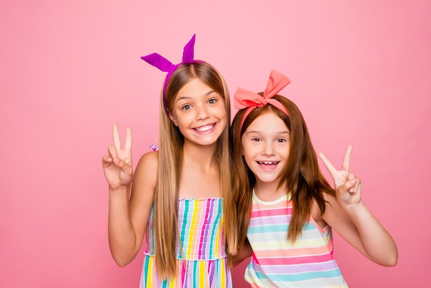 Portrait d'enfants charmants faisant v-signes portant jupe robe lumineuse isolé sur fond rose