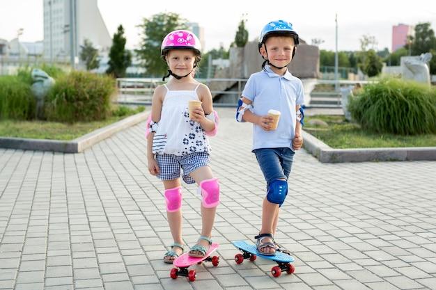 Portrait d'enfants dans le parc avec des patins, ils mangent de la glace