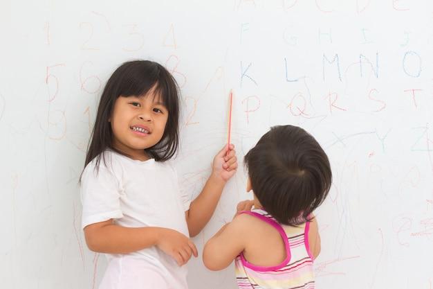 Portrait d'enfants écrivant sur le mur