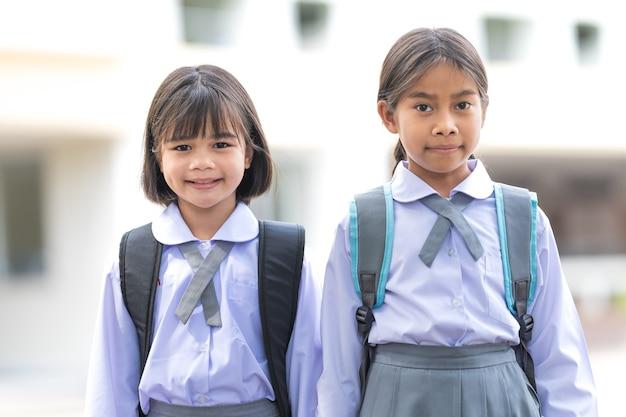 Portrait d'enfants étudiants en uniforme et sac à dos en regardant la caméra retourner à l'école après la quarantaine et le verrouillage de covid-19. retour à l'école, concept banque de photo