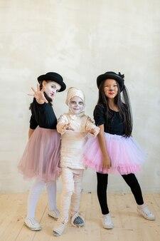 Portrait d'enfants interracial charismatiques souriants en costumes d'halloween cool se tenant ensemble et posant pour une photo de groupe à la fête