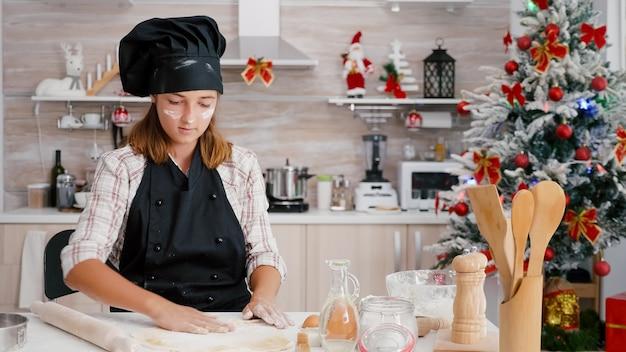 Portrait d'enfants mettant l'ingrédient de farine sur la pâte de pain d'épice faite maison