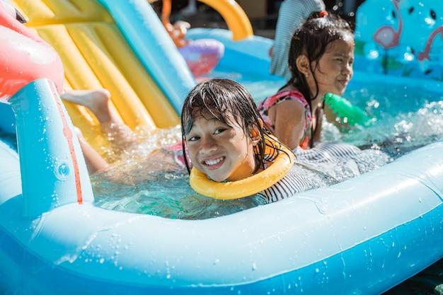 Portrait d'enfants très heureux de jouer à l'eau ensemble sur l'aire de jeux
