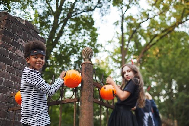 Portrait d'enfants vêtus de costumes d'halloween tenant sur une clôture tout en jouant avec des amis à l'extérieur, copiez l'espace