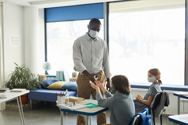 Portrait d'un enseignant désinfectant les mains des enfants dans la salle de classe, mesures de sécurité covid, espace de copie