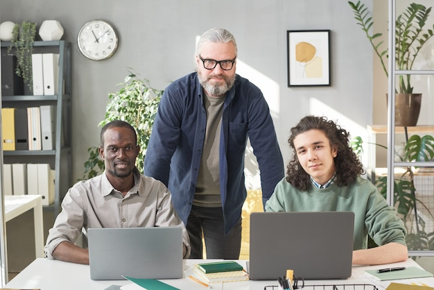 Portrait d'un enseignant mature regardant la caméra avec ses deux étudiants assis à la table avec des ordinateurs