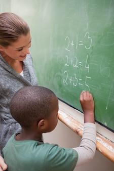Portrait d'un enseignant souriant et d'un élève faisant un ajout