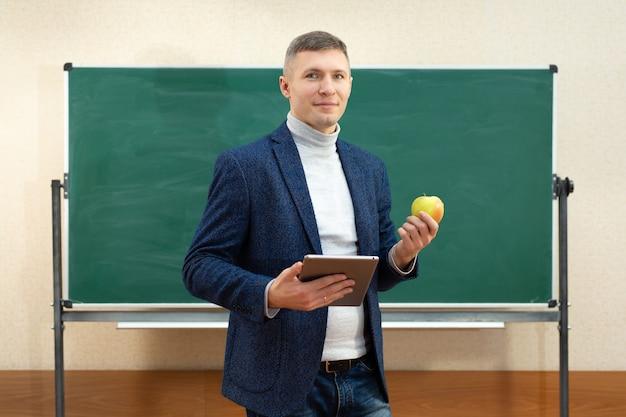 Portrait d'un enseignant souriant avec une tablette et une pomme verte