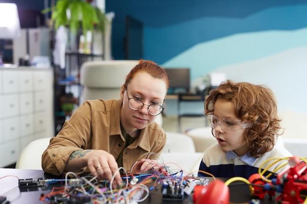 Portrait d'une enseignante aidant un garçon à construire un robot pendant les cours d'ingénierie à l'école, espace de copie