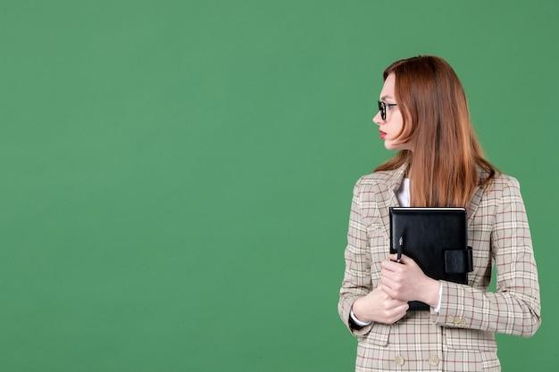 Portrait d'enseignante avec bloc-notes sur vert