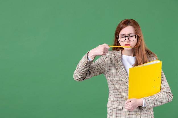 Portrait d'enseignante avec document jaune et crayon sur vert