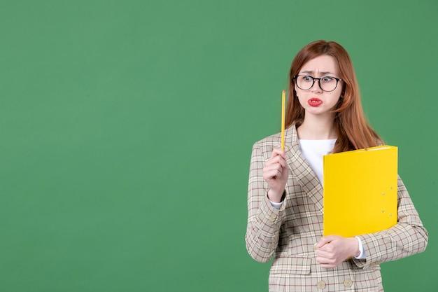 Portrait d'enseignante avec document jaune sur vert