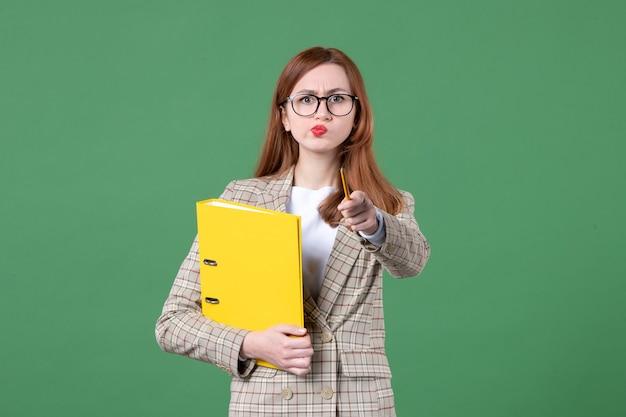 Portrait d'enseignante avec des fichiers jaunes sur vert