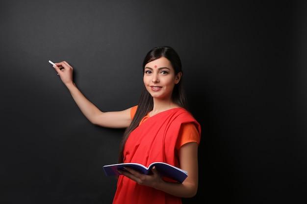 Portrait d'une enseignante indienne sur fond de tableau noir