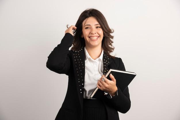 Portrait d'enseignante avec livre sur blanc.