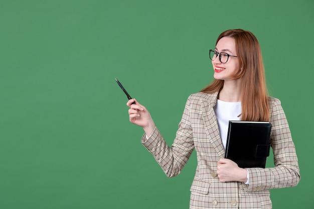 Portrait d'enseignante tenant le bloc-notes sur vert