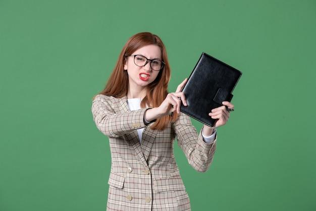 Portrait d'une enseignante tenant avec colère le bloc-notes sur vert