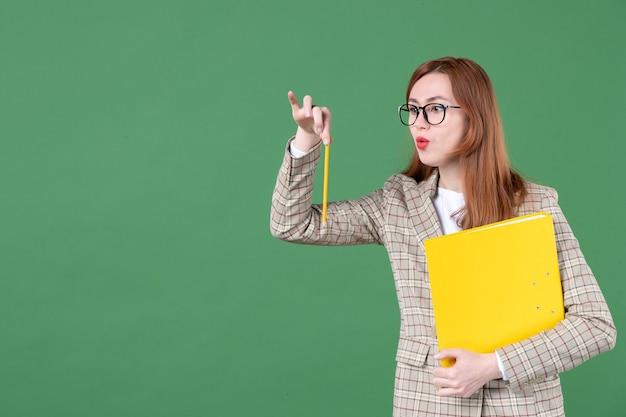 Portrait d'une enseignante tenant un document jaune et un crayon sur vert