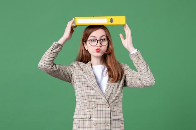 Portrait d'une enseignante tenant un document jaune sur sa tête verte
