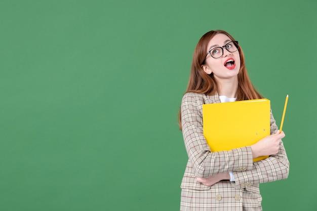 Portrait d'une enseignante tenant un document jaune sur vert