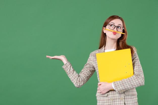 Portrait d'une enseignante tenant un fichier jaune sur vert
