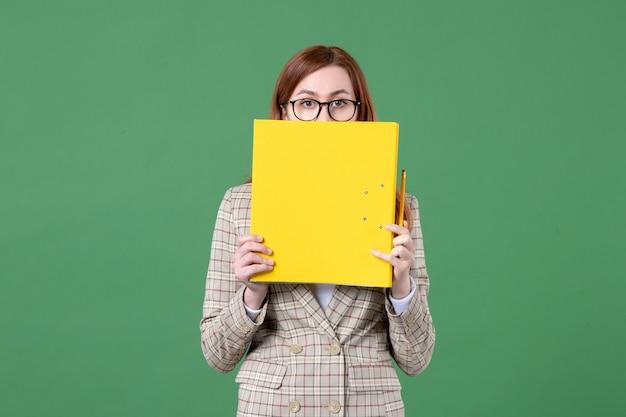 Portrait d'une enseignante tenant des fichiers jaunes et un crayon sur vert