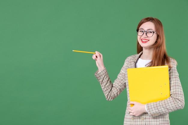Portrait d'une enseignante tenant joyeusement un document jaune sur vert