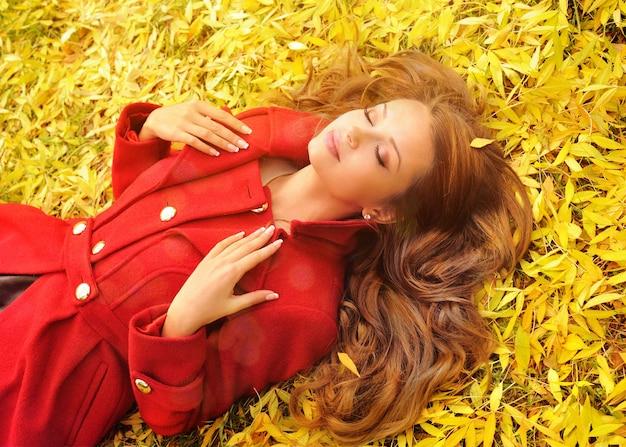 Portrait ensoleillé d'une jeune femme en manteau rouge couché dans les feuilles d'automne.