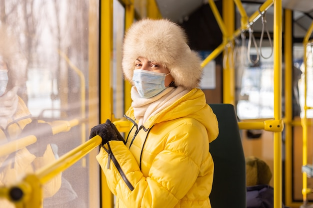 Portrait ensoleillé lumineux d'une jeune femme en vêtements chauds dans un bus de la ville un jour d'hiver
