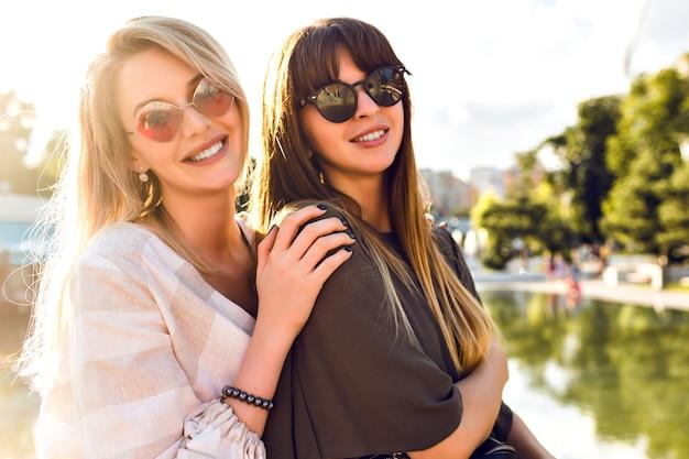 Portrait ensoleillé de mode de vie de couple heureux femme câlins et souriant, soeur meilleures filles amis, tenues élégantes et lunettes de soleil souriant fin profiter du temps ensemble, humeur de voyage.