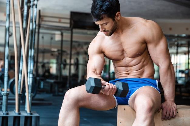Portrait d'un entraînement de bodybuilder musculaire masculin avec haltère dans une salle de fitness