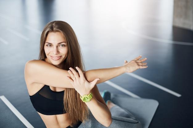Portrait de l'entraîneur de la femme de remise en forme du corps qui s'étend des bras se prépare pour une journée d'entraînement au travail acharné.