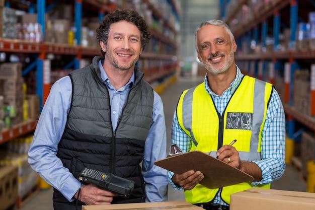 Portrait, entrepôt, ouvriers, debout, presse-papiers, barcode, scanner