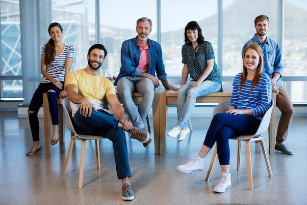 Portrait d'entreprise créative souriante assis sur une chaise et un bureau au bureau