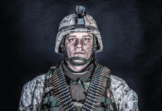 Portrait d'épaule d'un soldat de l'armée expérimenté, vétéran du conflit militaire, combattant marin qualifié en uniforme de camouflage en lambeaux, casque avancé et ceintures de munitions sur la poitrine, prise de vue en studio sur fond noir