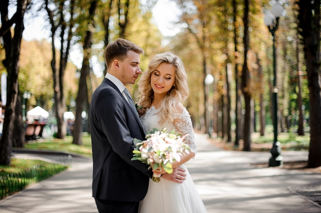 Portrait d'un époux embrassant une mariée blonde dans le parc