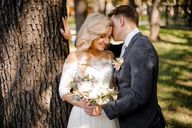 Portrait d'un époux embrassant une mariée blonde