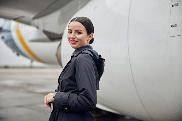 Portrait d'équipage d'avion caucasien heureux et confiant près de l'avion