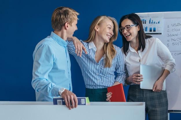 Portrait d'équipe d'affaires se tenant ensemble et riant
