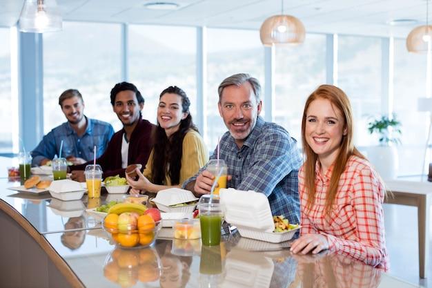 Portrait de l'équipe commerciale créative ayant un repas au bureau