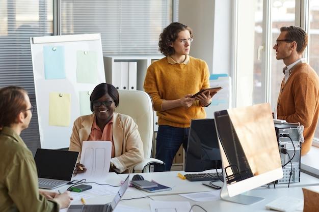 Portrait d'une équipe de développement informatique diversifiée collaborant sur un projet d'entreprise tout en travaillant dans un studio de production de logiciels