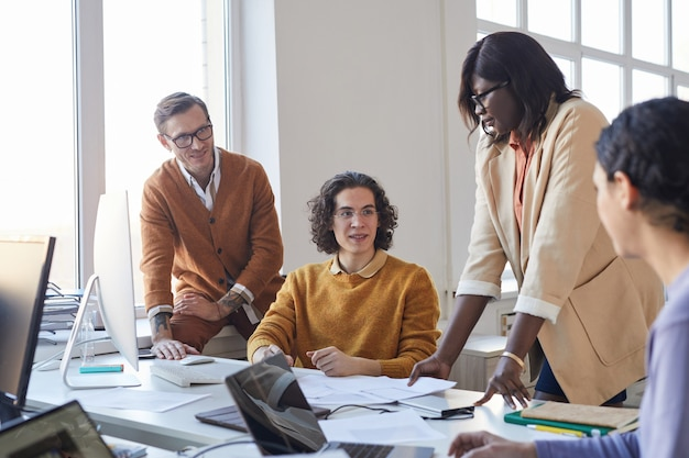 Portrait d'une équipe de développement de logiciels multiethnique discutant d'un projet tout en utilisant des ordinateurs dans un bureau moderne, espace de copie