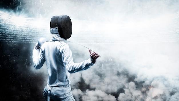 Portrait d'un escrimeur dans le contexte d'une arène sportive. fumée et étincelles, arrière-plan mystique. le concept d'escrime. vue arrière. technique mixte