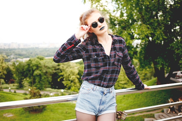 Portrait d'été de belle fille hipster maigre dans une chemise à carreaux et un short en jeans dans des lunettes de soleil élégantes et du rouge à lèvres bleu