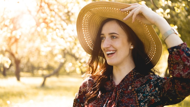Portrait d'été, belle jeune femme portant un chapeau de paille au coucher du soleil sur le jardin