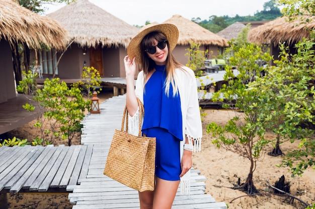Portrait d'été ensoleillé de jolie femme brune en chapeau de paille et sac boho tendance marchant dans une villa tropicale en thaïlande.